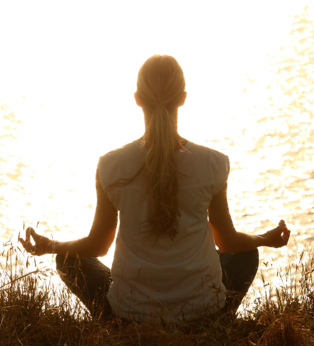 Meditierende Frau am See